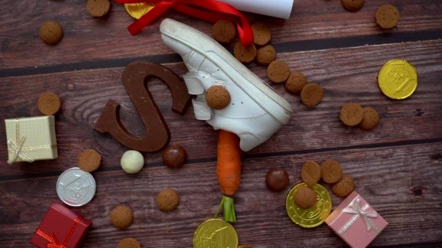 niederländischer urlaub sinterklaas hintergrund. rotation kinder schuh, karotten für santa pferd, geschenke, traditionelle süßigkeiten pepernoten und schokolade brief. schoentje zetten konzept. 4k video - nikolaus stiefel stock-videos und b-roll-filmmaterial