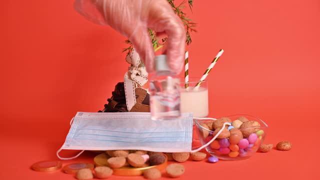stockvideo's en b-roll-footage met nederlandse feestdag sinterklaas. hildrens schoen met wortelen voor het paard van de kerstman, pepernoten en snoepjes. gehandschoende handen worden ingewreven met antiseptische, ontsmettingsmiddel en een beschermend masker. - pepernoten