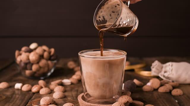 stockvideo's en b-roll-footage met nederlandse feestdag sinterklaas. pepernoten en zwarte aromatische koffie met melk. koffie wordt in melk gegoten. stop met mo. fullhd-beelden van hoge kwaliteit - pepernoten