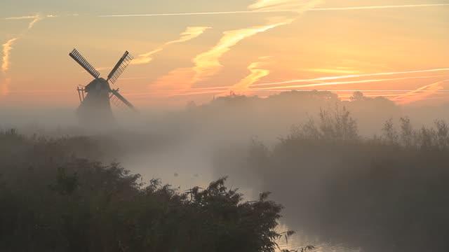 Dutch windmill Foggy, autumn sunrise near a traditional Dutch windmill at a small stream. marsh stock videos & royalty-free footage