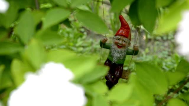 Dwarf in the garden on a swing