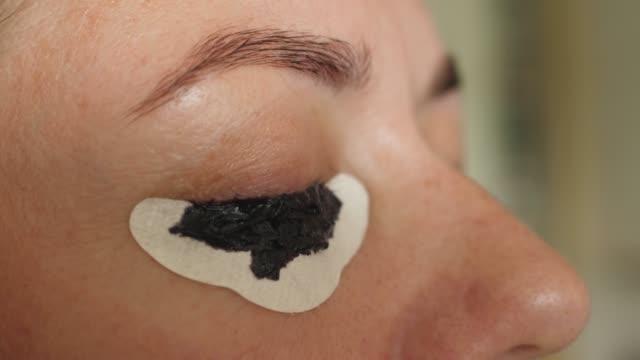 ヘナでまつげを染めるは、目の保護紙で適用適用 - まぶた点の映像素材/bロール