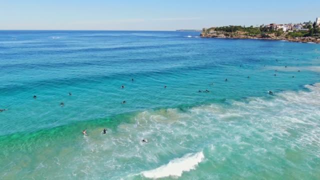 세계적으로 유명한 본다이 비치, 시드니, 뉴 사우스 웨일즈, 호주에서 좋은 파도를 기다리고 잠수복을 입고 서퍼를 통해 동적 4k 공중 무인 항공기 패닝 비행. 본다이 비치는 유명한 관광지입니� - 시드니 뉴사우스웨일스 스톡 비디오 및 b-롤 화면