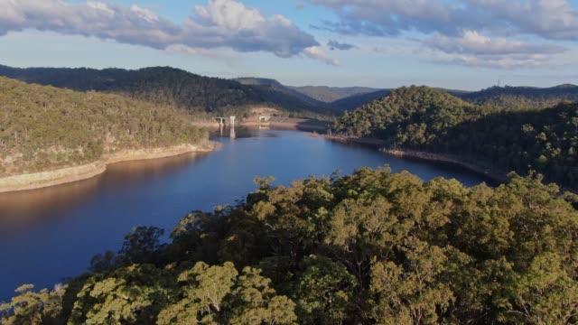 dynamischer drohnenflug über einen wald und ein mangrove creek dam reservoir zur wasserversorgung der bewohner der central coast in der nähe von sydney, new south wales, australien. niedriger wasserstand während der trockenheit. - staudamm stock-videos und b-roll-filmmaterial