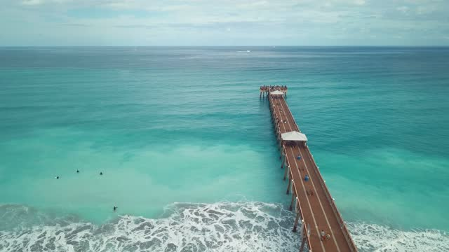Dynamic Aerial Views of Colorful Teal Ocean Waves Sweeping Across the Juno Beach, Florida Seashore & Pier at Mid-Day in January of 2021