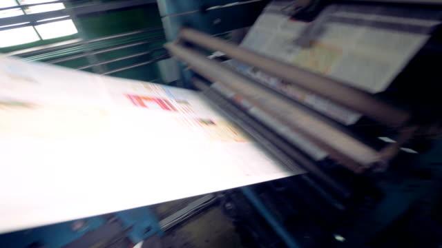 dynamisk kamera rörelse av en tryckta tidningar rullande på skrivarutrustning. - paper mass bildbanksvideor och videomaterial från bakom kulisserna