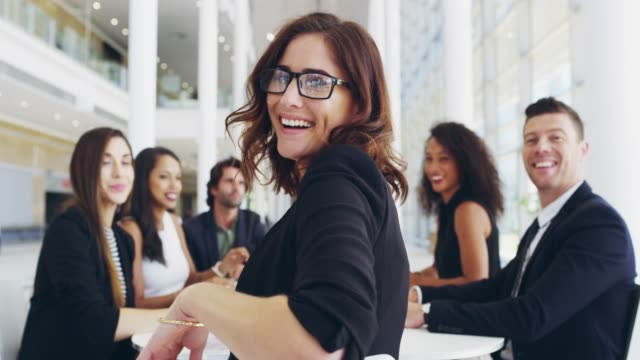 Each day is a chance to shine brighter in your career 4k video footage of a young businesswoman smiling in an office during a meeting with her colleagues in the background employee stock videos & royalty-free footage