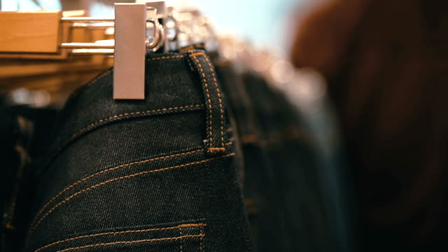 eans hanging on hangers on the rack in the clothing store. - jeans video stock e b–roll
