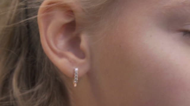 Ear and eye of young blonde girl, extreme closeup view Ear and eye of young blonde girl, extreme closeup view. Female child with golden earring in ear, cropped view ear stock videos & royalty-free footage