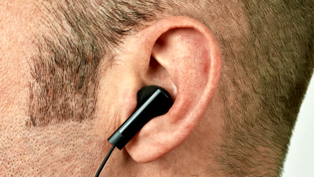 Ear with earphone vibrating and jumping to music video