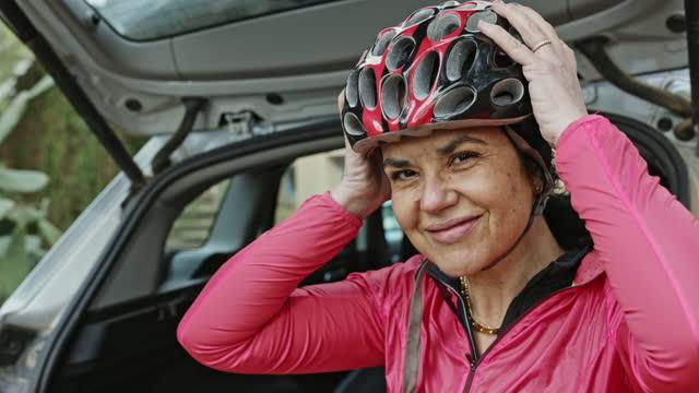 la ciclista dei primi anni '50 che si mette il casco prima dell'allenamento - indipendenza video stock e b–roll