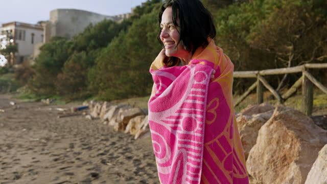 Early 50s Hispanic Woman After Early Morning Swim Partial front view of invigorated sportswoman in swimsuit, wrapped in towel, drying off, and smiling as she stands on Costa Brava beach. independence stock videos & royalty-free footage