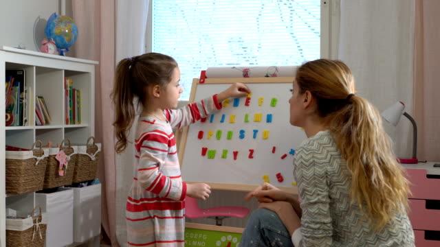 barns tidiga utveckling. ung kvinna undervisning barnet alfabetet - förskoleelev bildbanksvideor och videomaterial från bakom kulisserna