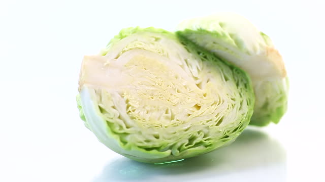 early green cabbage cut in half swing on a white background - капустные стоковые видео и кадры b-roll