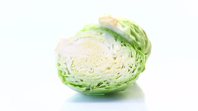 early green cabbage cut in half swing on a white background video