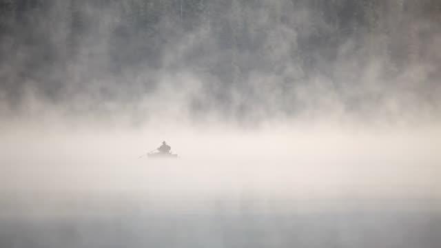 HD early morning fishing on lake in fog video