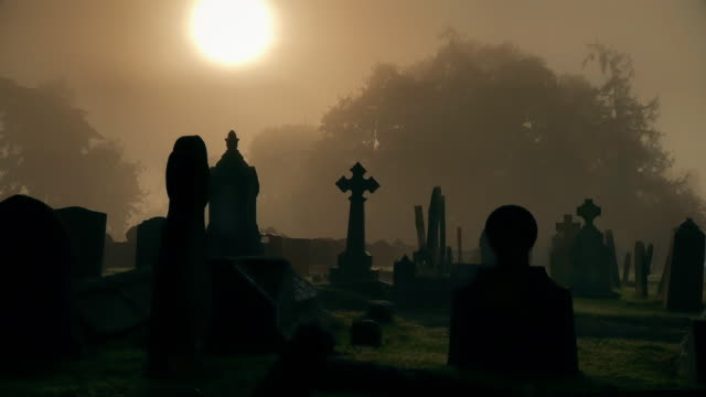 Early morning graveyard with sun through the mist and silhouette tombstones