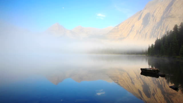 Early morning mist rising from lake surface with mountains glowing video
