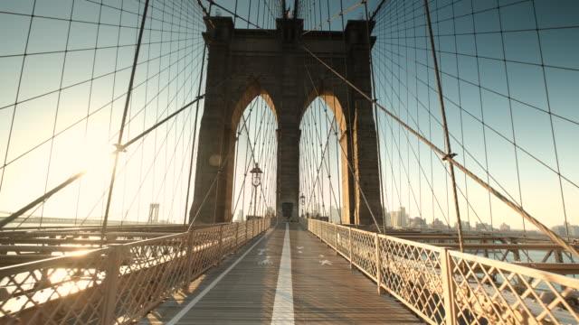 vídeos de stock, filmes e b-roll de o sol da manhã nasce no caminho da ponte do brooklyn sobre o east river ligando manhattan nova york ao brooklyn eua - new york city