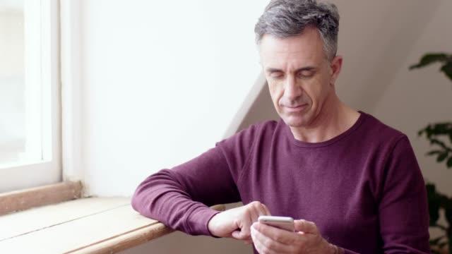 vídeos de stock e filmes b-roll de early morning text messages - homem casual standing sorrir