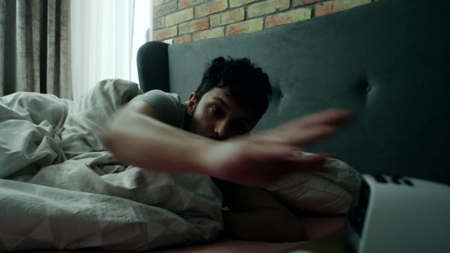 Early morning Young man woken by the alarm clock in the morning. dawn stock videos & royalty-free footage