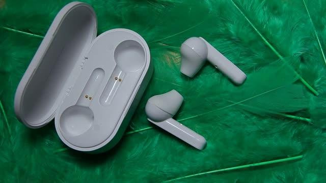 earphones green bird feather background hd footage - auricolari wireless video stock e b–roll