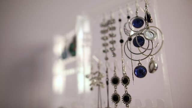 Earrings hanging on the stand in in jewelry store