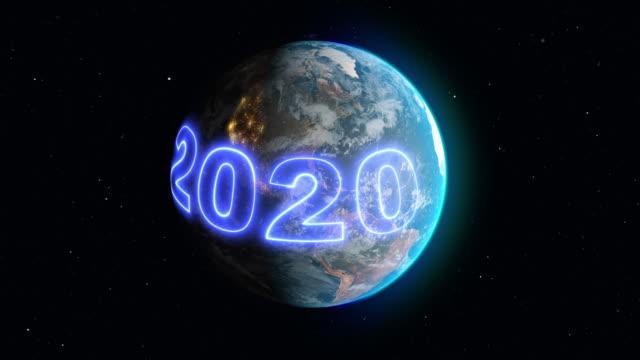 stockvideo's en b-roll-footage met aarde in een baan met 2020 nieuwjaar neon banner - new world