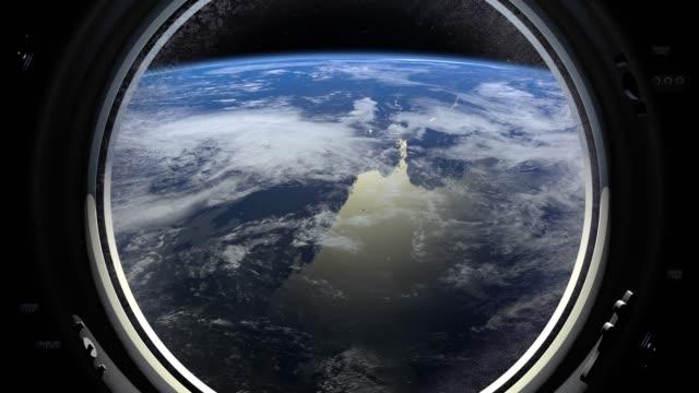La Terre à travers la grande fenêtre du hublot du vaisseau spatial. La station spatiale internationale se déplace vers la droite. Ambiance réaliste. Iss. 4K. - Vidéo