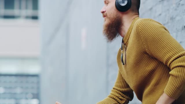 Easing in to some chilled beats 4k video footage of a confident young man wearing headphones while listening to music bluetooth stock videos & royalty-free footage