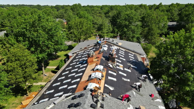 East Brunswick NJ US. 20 JUNE 2020: Roof repairs old roof replacement with new shingles of an apartment building
