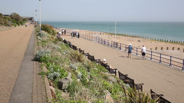 eastbourne east sussex with people walking on the seafront promenade - sud est video stock e b–roll