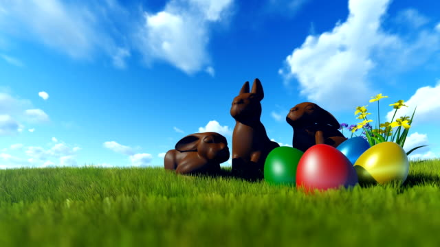 Easter Eggs and Chocolate Bunnies on green meadow against blue sky video