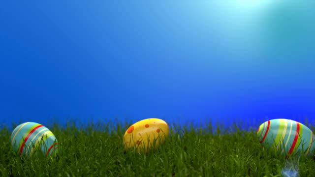 çimenlerin üzerinde paskalya yumurtaları. paskalya yumurtaları yeşil mısır gevreği ile kaplı yamaç aşağı slayt. güneşli pozitif iklim. - süslü püslü stok videoları ve detay görüntü çekimi