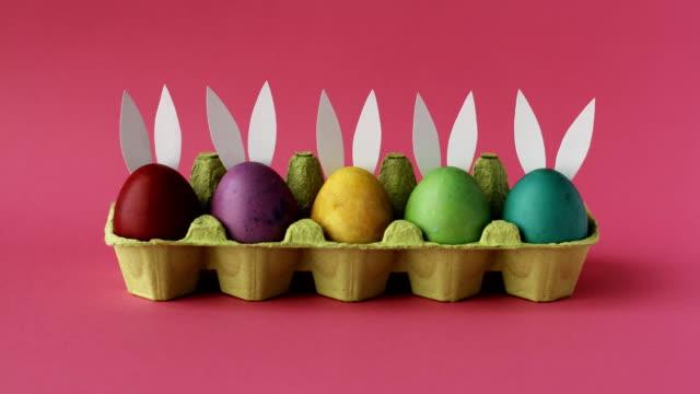 le uova di pasqua con orecchie di coniglio variano su sfondo rosa. buona pasqua - easter video stock e b–roll