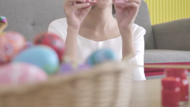 Easter, holidays and people concept. Tilt up shot, portrait of cheerful happy girl wearing bunny ears headband sitting on the sofa, choosing easter eggs decorated colourful of handmade for festival.