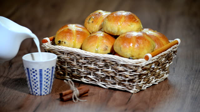 Easter Hot Cross Buns in a Basket. Pour milk into a Cup Easter Hot Cross Buns in a Basket. Pour milk into a Cup bun bread stock videos & royalty-free footage