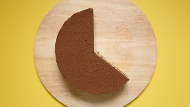 TOP VIEW: Eating a layer cake on a yellow background - Stop motion video