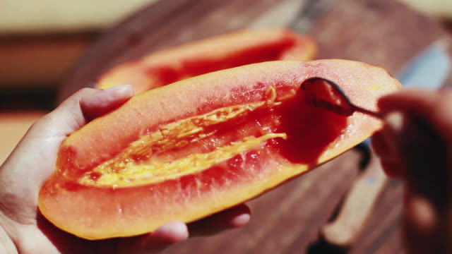 Eating a papaya fruit with spoon on wooden table. 1920x1080 video
