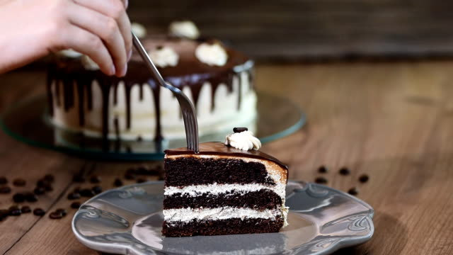 포크와 초콜릿 케이크 한 조각을 먹고 - cake 스톡 비디오 및 b-롤 화면