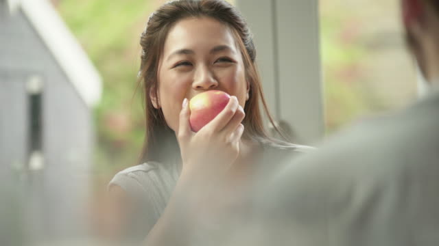 eating apple with someone Close up stock video clip of a young Asian woman eating an apple while chatting to a friend across the table. healthy lifestyle stock videos & royalty-free footage