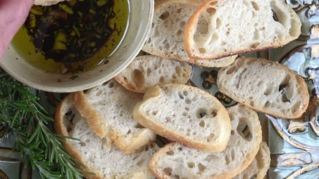 먹는 장인 잘라 올리브 오일과 발사믹 식초와 함께 롤 빵 - 식빵 한 덩어리 스톡 비디오 및 b-롤 화면