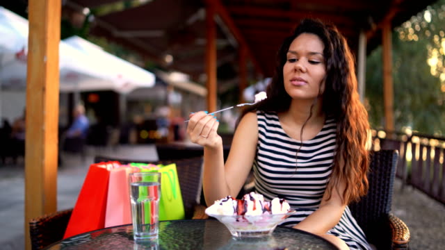 Eating banana split Young woman is sitting in downtown sidewalk cafe and eating banana split indulgence stock videos & royalty-free footage