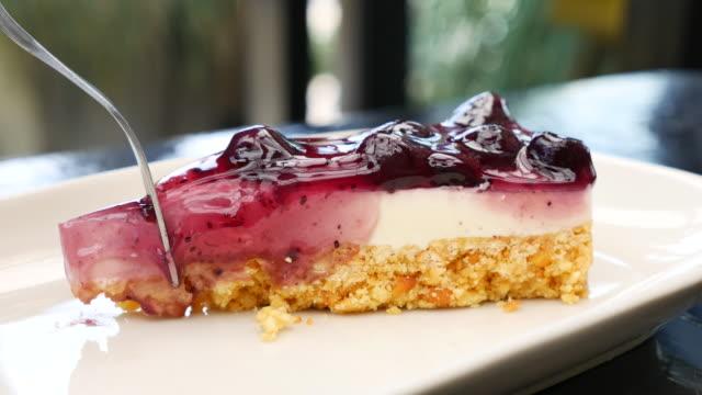 eating blueberry cheese cake with serving and cutting cake - sernik filmów i materiałów b-roll