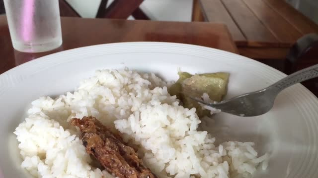 Eating boiled rice with Thai style deep fried minced pork