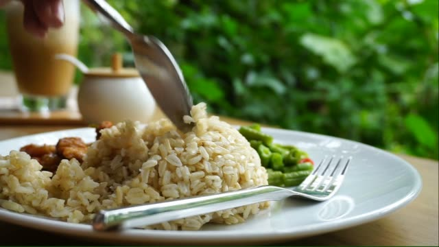 Eating brown rice with spoon and fork video