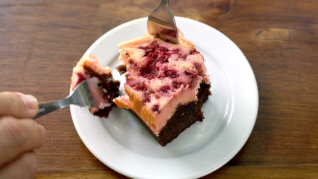 Eating brownie raspberries cake.