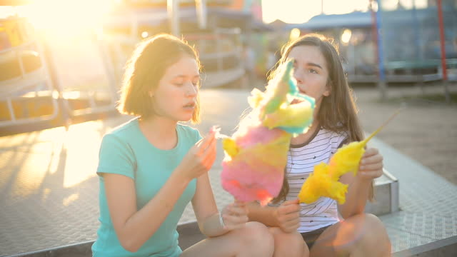 Eating cotton candy and having fun at the amusement park Eating cotton candy and having fun at the amusement park cotton candy stock videos & royalty-free footage