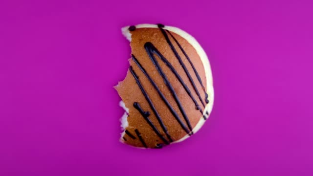 eating fresh donut on violet background. time-lapse. bakery concept. 4k, uhd - sweet pie stock videos & royalty-free footage