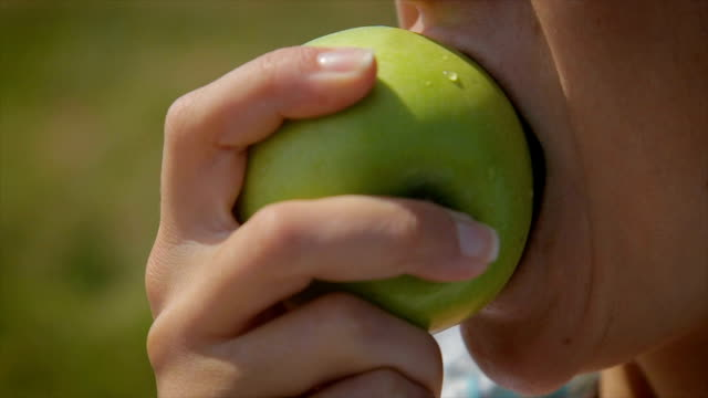 eating green apple.close up - denti video stock e b–roll